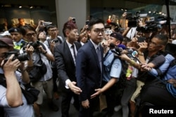 FILE - Andy Chan is surrounded by photographers as he leaves th   e Foreign Correspondents' Club in Hong Kong, Aug. 14, 2018.