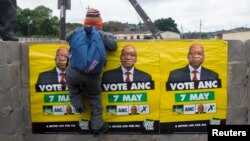 African National Congress (ANC) election posters featuring images of South Africa's President Jacob Zuma are displayed on a wall as a school boy climbs over it in Embo, May 6, 2014.