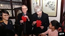 2018年2月2日,英國首相特蕾莎梅和她的丈夫菲利普梅在上海豫園觀看學生剪紙,手裡拿著福字。