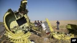 Malezya uçağının parçalarını inceleyen Avustralyalı ve Hollandalı polisler