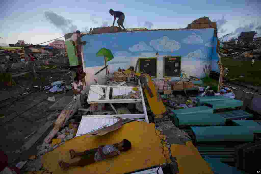 Children who survived Typhoon Haiyan play on top of the ruins of their destroyed primary school in Guiuan, Philippines, Nov. 14, 2013.