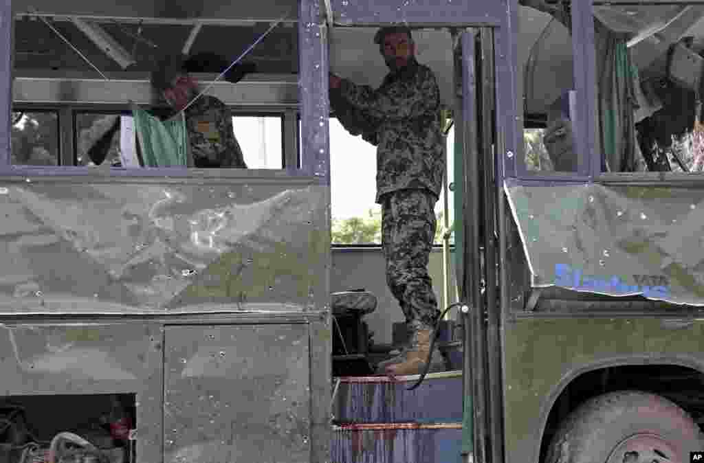 Afghan National Army soldiers prepare to remove a destroyed military bus after a suicide attack in Kabul, June 2, 2014.