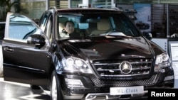 一名男子在北京一家奔驰汽车4S店体验一辆ML350汽车。(2012年2月17日)