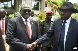 FILE - South Sudan's First Vice President Riek Machar (L) and President Salva Kiir (R) shake hands following the first meeting of a new transitional coalition government, in the capital Juba, South Sudan, April 29, 2016.