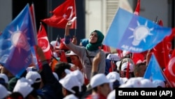 Supporters listen to Turkey's Prime Minister and leader of the ruling Justice and Development Party, Ahmet Davutoglu, as he addresses a rally before the Nov. 1 general elections, in Bursa, Turkey.