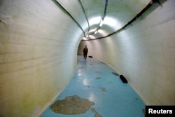 FILE - A member of the Armed Forces of Bosnia and Herzegovina walks through a tunnel in Josip Broz Tito's underground secret bunker (ARK) in Konjic, Oct. 16, 2014. In the early 1950s Tito ordered the building of the secret bunker to safeguard the country's ruling class in case of a nuclear attack.