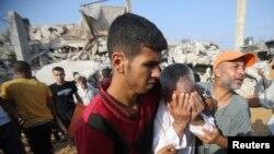 Seorang pria Palestina menangis, sementara warga lainnya mencari korban di antara reruntuhan setelah serangan udara Israel di sebuah permukiman di Rafah, Jalur Gaza (29/7).