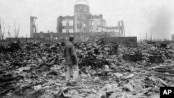 រូបឯកសារ៖ រូបថតពីឆ្នាំ១៩៤៥ បង្ហាញពីរូបថតអ្នកយកព័ត៌មានឈរនៅពីមុខអាគារដែលធ្លាប់ជារោងកុននៅទីក្រុង Hiroshima ប៉ុន្មានខែក្រោយពេលគ្រាប់បែកបរមាណូត្រូវបានទម្លាក់លើក្រុងនេះ កាលពីថ្ងៃទី៦ ខែសីហា ឆ្នាំ១៩៤៥។