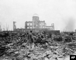 This Sept. 8, 1945 picture shows an allied correspondent standing in the rubble in front of the shell of a building that once was a movie theater in Hiroshima, Japan, a month after the first atomic bomb ever used in warfare was dropped by the U.S.