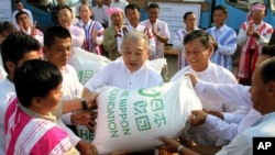 In this photo taken Feb. 12, 2013, Yohei Sasakawa, center, Japan's Goodwill Ambassador for the Welfare of the National Races in Myanmar and Chairman of the Nippon Foundation, donates sacks of rice to locals in Hpa-an, Karen State, Burma.