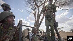 A Kenyan army soldier, left, looks up as a Somali government soldier, right, climbs across the vehicle that they are sharing, and another Somali government soldier prepares to drive, center, in Tabda, inside Somalia, February 20, 2012.