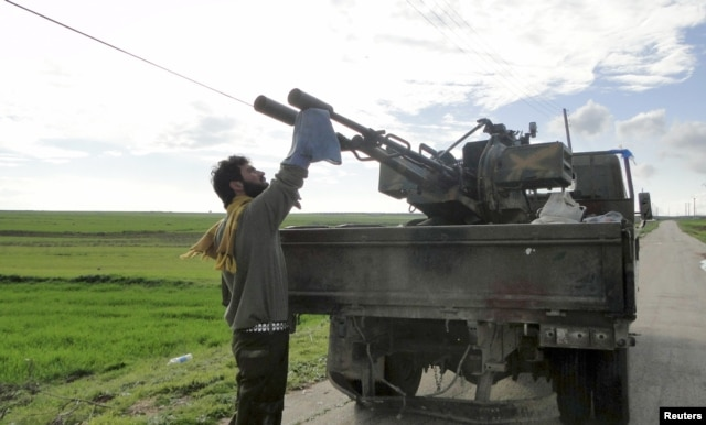 FILE - A Free Syrian Army fighter cleans an anti-aircraft artillery gun near the Menagh military airport in Aleppo's countryside, Feb. 17, 2013.