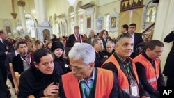 A Syrian woman (L) speaks with an Arab league observer, (R) who attends with other observers a mass prayer for the people and army soldiers who were killed during the violence around the country, at the Holy Cross Church, in Damascus, January 9, 2012