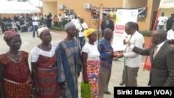 Des bénéficiaires reçoivent leur kit des mains du ministre Jean-Claire Kouassi. (VOA/ Siriki Barro)