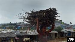 Rohingya refugee child carries wood as rain falls at Jamtoli refugee camp in Ukhia