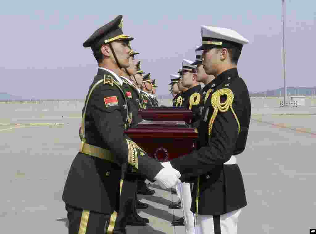 Chinese honor guards, left, receive caskets containing the remains of Chinese soldiers from South Korean honor guards during the handing over ceremony at the Incheon International Airport in Incheon, South Korea. The remains of 28 Chinese soldiers killed during the 1950-53 Korean War were returned home for permanent burial.
