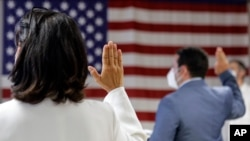 FILE- In this July 2, 2020, file photo, people take the oath of citizenship during a naturalization ceremony at U.S. Citizenship and Immigration Service's Field Office in New York.