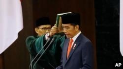 Presiden Indonesia Joko Widodo membacakan sumpahnya saat upacara pelantikannya di gedung parlemen di Jakarta, 20 Oktober 2019. (Foto: AP)