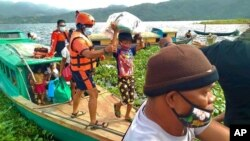 In this Philippine Coast Guard photo, families are evacuated to safer ground in Camarines Sur province, eastern Philippines, Oct. 31, 2020, as Typhoon Goni approaches.