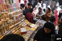 Women buy jewelry at the Baghbanpura Bazaar ahead of the Muslim Eid al-Fitr festival in Lahore, Pakistan, May 21, 2020.