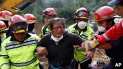 Nhân viên cứu hộ giúp một phụ nữ sau khi bà xác nhận 2 thi thể của thân nhận tại hiện trường vụ đất chuồi ở Cambray, ngoại ô Santa Catarina Pinula, Guatemala, ngày 3/10/2015.