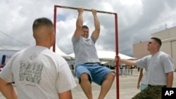 FILE - Matt Elam, center, competes in a US Marine pull-up contest while Marine recruiters Sgt. Marco Hartanto, left, and Gysgt. Brian Lancioni watch during BayFest 2006 held at Marine Corps Base Hawaii, Tuesday, July 4, 2006, in Kaneohe, Hawaii.