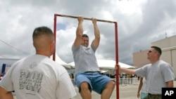 在夏威夷一處基地,一名年輕人在海軍陸戰隊招兵人員的注視下參加單槓引體向上比賽。