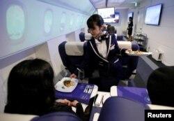 """Seorang pramugari menyajikan makanan pembuka kepada para tamu """"First Airlines"""", penerbangan kelas satu realitas maya di Tokyo, Japan, 14 Februari 2018."""