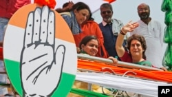 Congress party General Secretary and eastern Uttar Pradesh state in-charge Priyanka Gandhi Vadra, right, waves to party workers as she undertakes a steamer ride in the River Ganges from Manaiya, 25 kilometers (15.6 miles) from Prayagraj, India, March 18, 2019.