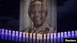 Candles are lit under a portrait of former South African President Nelson Mandela in his ancestral village of Qunu, Dec. 15, 2013.