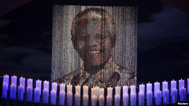Candles are lit under a portrait of former South African President Nelson Mandela in his ancestral village of Qunu December 15, 2013.