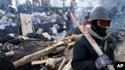 一名抗议者面对乌克兰防暴警察守卫在基辅的路障前。