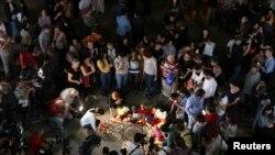 Des personnes apportent des fleurs et des bougies lors d'une cérémonie à la mémoire du chanteur Charles Aznavour, sur la place Charles Aznavour à Erevan, en Arménie, le 1er octobre 2018.