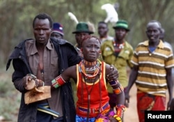 A man holds onto a girl as he brings her back to her family home after she tried to escape when she realized she is to be married, about 80 km (50 miles) from the town of Marigat in Baringo County, Dec. 7, 2014.