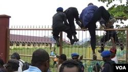 Para peserta Kongres Rakyat Papua di Abepura melompati pagar saat petugas keamanan dikerahkan untuk menertibkan kerusuhan di acara Kongres itu (19/10). Sedikitnya 6 orang tewas dalam insiden di Abepura.