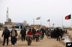 FILE - Afghans return to Afghanistan at the Islam Qala border with Iran, in the western Herat province, Feb. 20, 2019. Security officials worry that Iranian-backed Afghan veterans of the war in Syria will one day become a secret army for Tehran in Afghanistan itself.