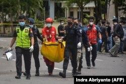 Polisi membawa tas berisi jasad terduga pelaku bom bunuh diri pasca ledakan di luar sebuah gereja di Makassar pada 28 Maret 2021. (Foto: AFP/Indra Abriyanto)