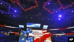 Republican National Committee Chairman Reince Priebus (L) and convention CEO William Harris unveil the stage and podium for the 2012 Republican National Convention, August 20, 2012, at the Tampa Bay Times Forum in Tampa, Florida.