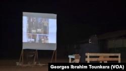 Une vidéo est protégée sur un écran lors d'une séance de sensibilisation sur le danger de l'immigration clandestine à Daloa, Côte d'Ivoire, septembre 2017. (VOA/ Georges Ibrahim Tounkara)