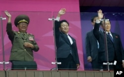 N. Korea's National Defense Commission Vice Chairman Hwang Pyong So, left, and N. Korea's Workers Party secretaries, Choe Ryong Hae and Kim Yang Gon wave as their team marches into the stadium at Asian Games in Incheon, S. Korea, Oct. 4, 2014.