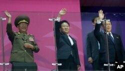 在仁川亚运会上,朝鲜军队次帅、国防委员会副委员长、军队总政治局长黄炳誓(左)、朝鲜劳动党中央书记崔龙海(中)、金养建在朝鲜队入场时挥手致意。