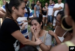 Residents react with relief after learning that their relatives survived the two collapsed buildings in the Muzema neighborhood, Rio de Janeiro, Brazil, April 12, 2019.