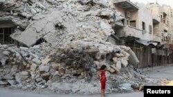 Seorang anak perempuan di depan gedung yang hancur akibat serangan pasukan pemerintah Suriah di kota Ariha, provinsi Idlib. (Foto: Dok)