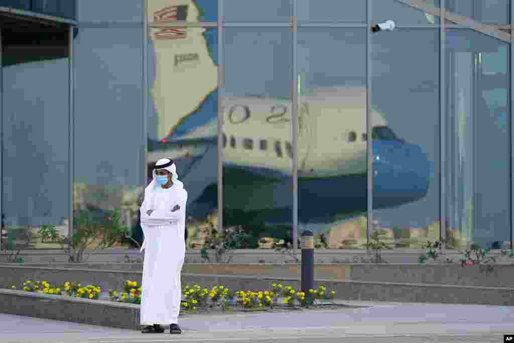 A man stands on a tarmac as Secretary of State Mike Pompeo's plane is reflected in windows at Al Bateen Executive Airport in Abu Dhabi, United Arab Emirates. Pompeo is visiting the United Arab Emirates as part of a trip to Europe and the Middle East.