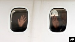 Người tị nạn Eritrea vẫy tay trước khi một máy bay của Italia chuẩn bị đưa họ tới Thụy Điển tại sân bay Ciampino, Rome, hôm 9/10.