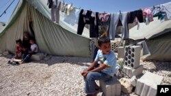一名敘利亞男童坐在與敘利亞邊境附近的黎巴嫩城鎮臨時居所外面