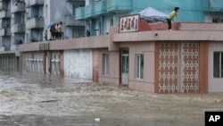 北韓人爬到屋頂避洪水