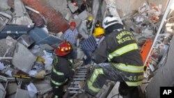 Regu pemadam kebakaran dari sektor Tacubaya dan para pekerja lainnya melakukan pencarian korban dengan menggali bangunan yang runtuh akibat ledakan di kantor pusat perusahaan minyak negara Meksiko, PEMEX, 31 Januari 2013. (AP Photo/Guillermo Gutierrez).