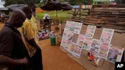 Men read newspaper headlines after recent elections near the entrance to the local zoo, right rear, in Abidjan, Ivory Coast, Monday, Oct. 26, 2015.