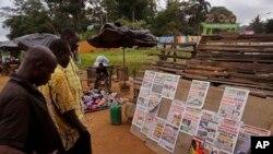 Beberapa pria membaca berita utama di halaman depan surat kabar lokal yang mengulas berita tentang pemilihan umum di Abidjan, Pantai Gading (26/10).